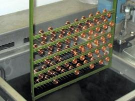 Abbildung zeigt einen Galvanik-Rahmen mit aufgesteckt Kupferdrehteilen.
